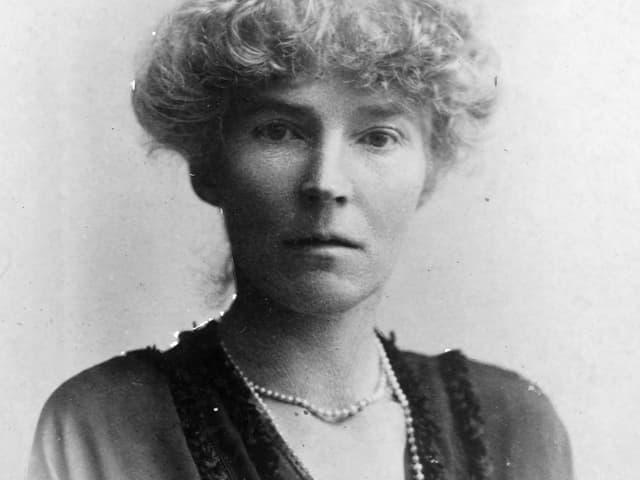 Schwarz-weiss Porträt einer jüngeren Frau mit Perlenkette um den Hals