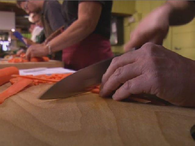 Mann schneidet auf einem Holzbrett Karotten.