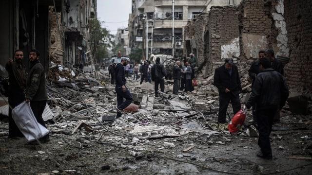 Zerstörte Gebäude und aufräumende Menschen