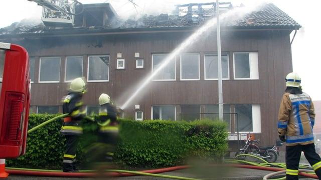 Brand Mehrfamilienhaus in Niederlenz 2012, im Bild Feuerwehrleute und ein Brandermittler