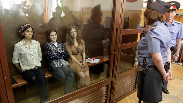 Mitglieder der Band Pussy Riot während des Prozesses in einer Glaskabine, Wachpersonal davor.