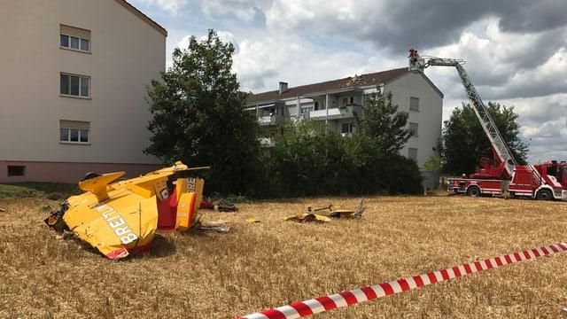 Links das Flugzeugwrack, rechts das beschädigte Hausdach.
