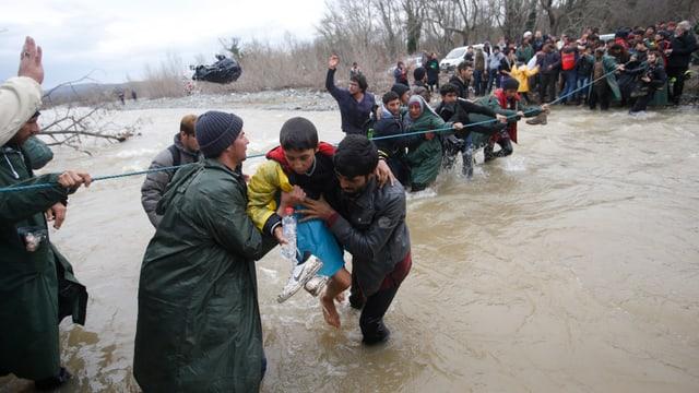 Menschen durschschreiten einen kniehohen Fluss und halten sich dabei an einem Seil fest.