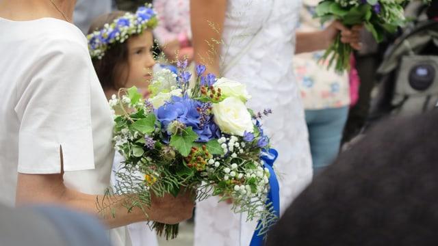 Blumenstrauss, dahinter Mädchen in Weiss.
