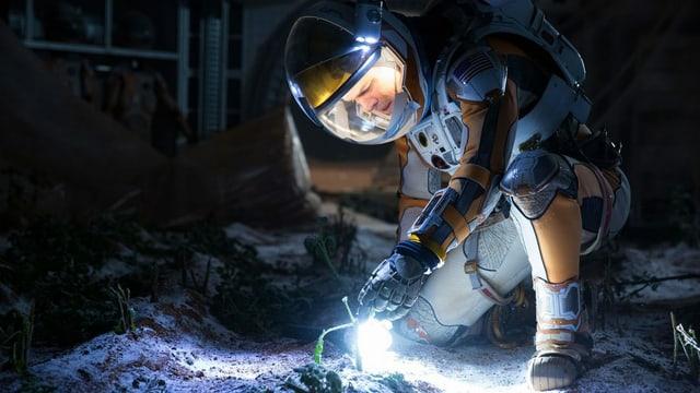 ein Astronaut begutachtet eine Pflanze