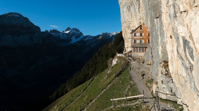 Berggasthaus Aescher im Alpstein/AI: Ein Holzhaus klebt am Fels, ein Wanderweg führt hinzu, im Hintergrund schneebedeckte Berge.
