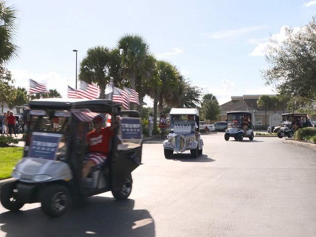 mit Flaggen und Plakaten geschmückte Golfwagen in einer Seniorensiedlung
