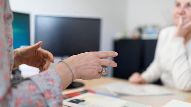 Zwei Frauen im Gespräch an einem Bürotisch.