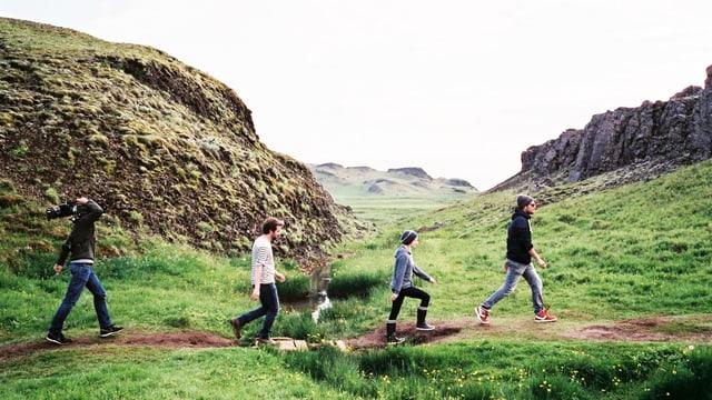 Vier Personen laufen durch eine grüne Landschaft.
