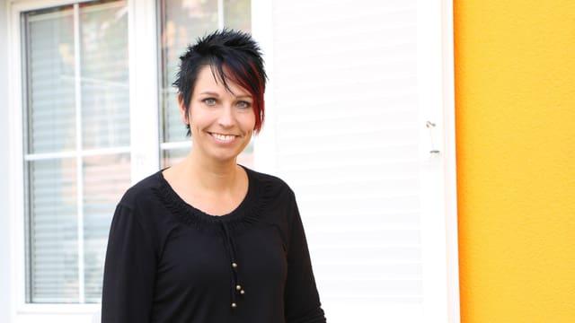 Sandra Sollberger vor gelber Fassade