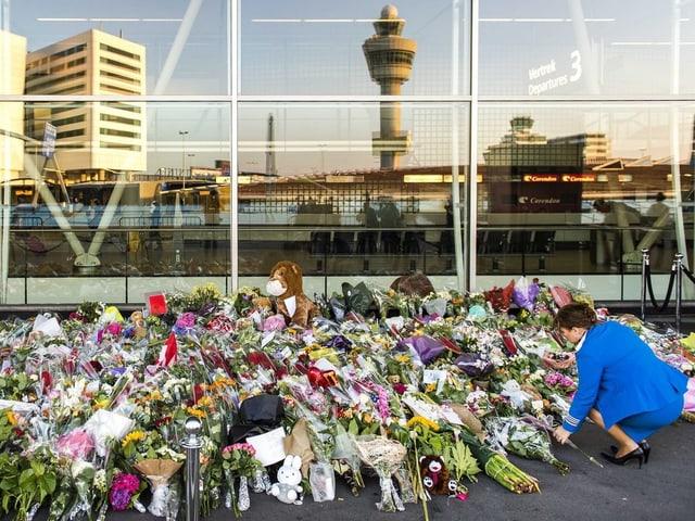 Eine Frau legt Blumen am Amsterdamer Flughafen Schiphol nieder. Seit dem Absturz der Boeing in der Ostukraine ist er zum nationalen Denkmal geworden.