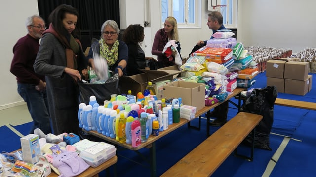 Personen sortieren und verpacken Hygieneartikel in Kartonkisten.