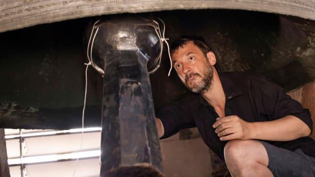 Peter Conradin Zumthor schiebt den Klöppel an die Glocke und testet so den Klang.