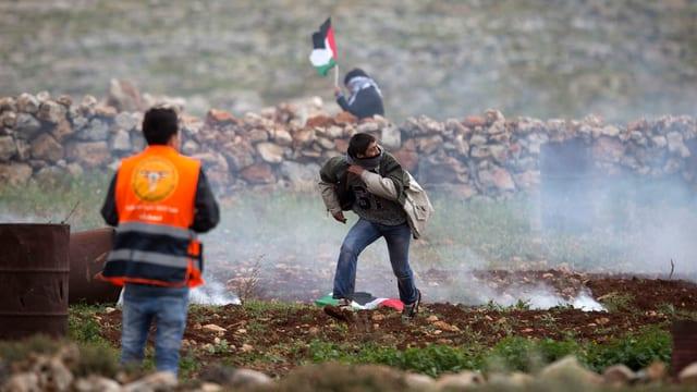Ein Palästinenser rennt von einer Mauer weg.