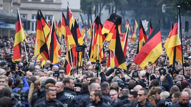 Eine Demonstration mit vielen Menschen, Polizei und vielen Deutschland-Fahnen.