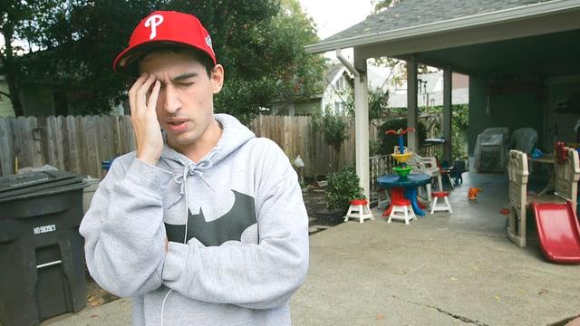Junger Mann mit roter Baseballcap greift sich an den Kopf.