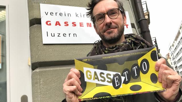 """Roger Lütolf vom Verein Kirchliche Gassenarbeit Luzern mit einer Comic-Spezialausgabe der """"Gasseziitig"""" in der Hand."""