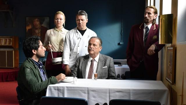 Filmszene: zwei Männer sitzen am tisch und drei Leute stehen daneben.
