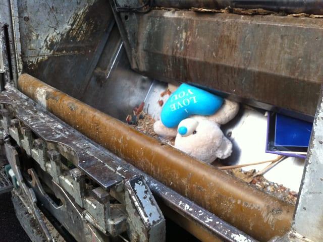 Ein Plüschbär im Abfallwagen.