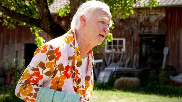 Schauspieler Robert Gustafsson in geblümtem Hemd mit Handtuch über dem Arm.