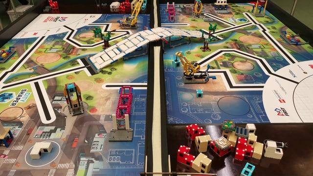 Ort der Wettkämpfe: Zwei Tische mit einer symbolhaft dargestellten Stadt-Landschaft.