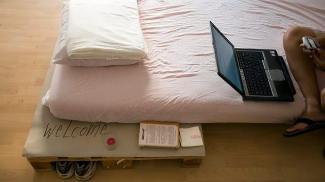Man sieht ein Bett auf einem einfachen Bettgestell und das Knie einer Person, die auf dem Bett sitzt