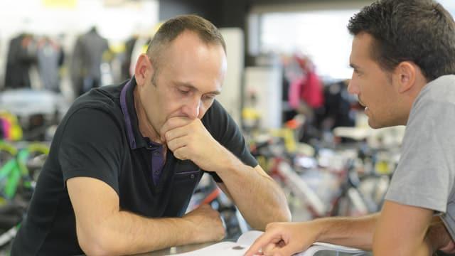 Zwei Männer diskutieren über eine Offerte