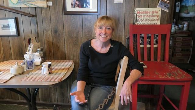 Nina Mc Coy sitzt lachend an einem Tisch.