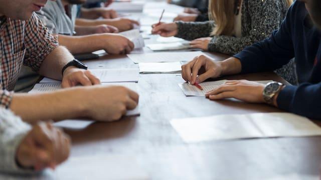 Blick auf langen Tisch mit Leuten, die Wahlzettel kontrollieren.