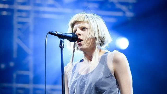 Blonde Musikerin singt in Mikrofon vor blauem Hintergurnd