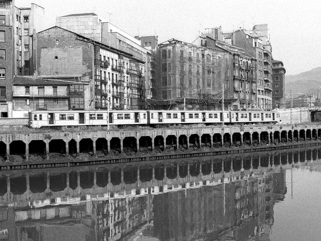 Zug steht am Ufer des Flusses, dahinter vierstöckige Wohnhäuser