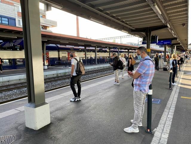Pendler warten am Bahnhof Uster.