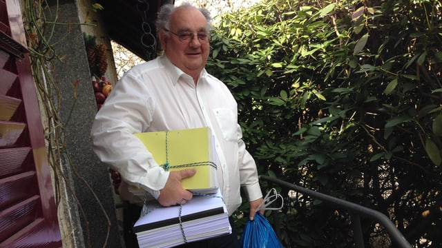 Ein Mann mit gebündeltem Altpapier vor seiner Haustüre.