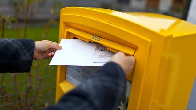Eine Frau wirft einen Brief in einen gelben Post-Briefkasten.