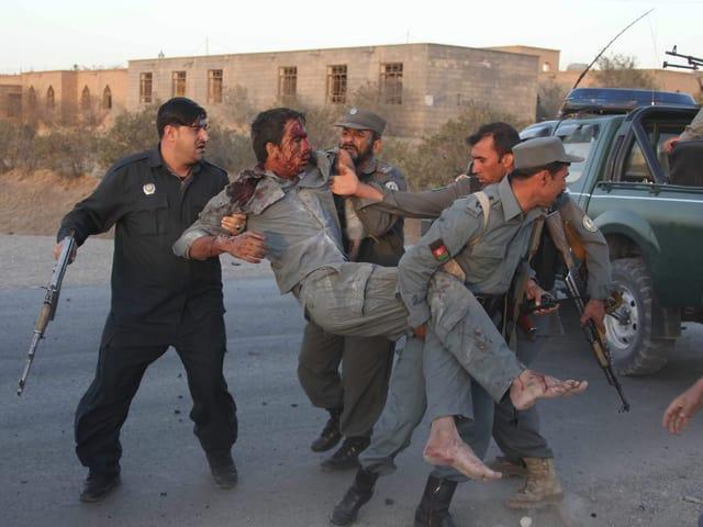 Afghanische Soldaten und Polizisten bergen einen Verletzten.
