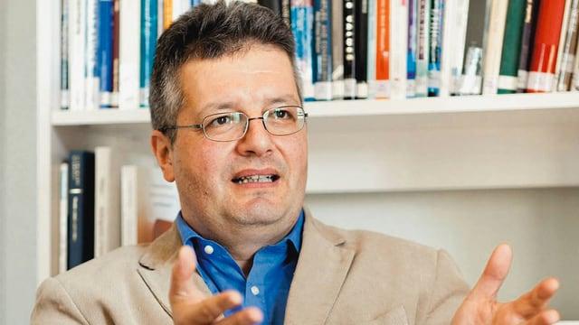 Philosoph Peter Schaber gestikulirened vor einem Büchergestell.