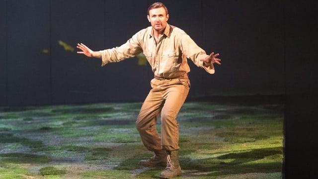 Ein Mann im beigen Outfit steht auf der Bühne. Szene aus «Peter Gynt».