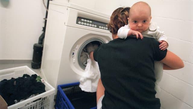 Ina mamma che tegn in pop e metta resti en la maschina da lavar resti.