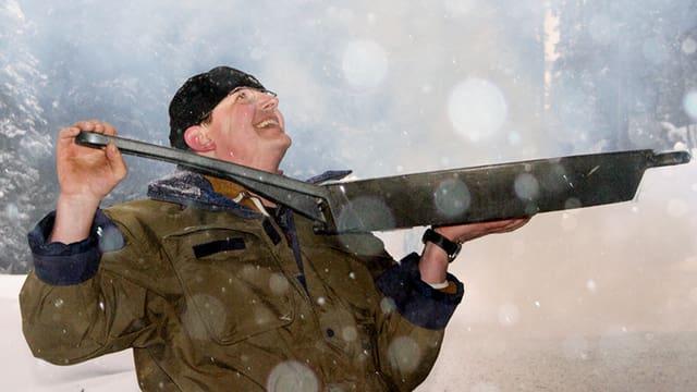 Mann hält grosse Bratpfanne in den Schnee