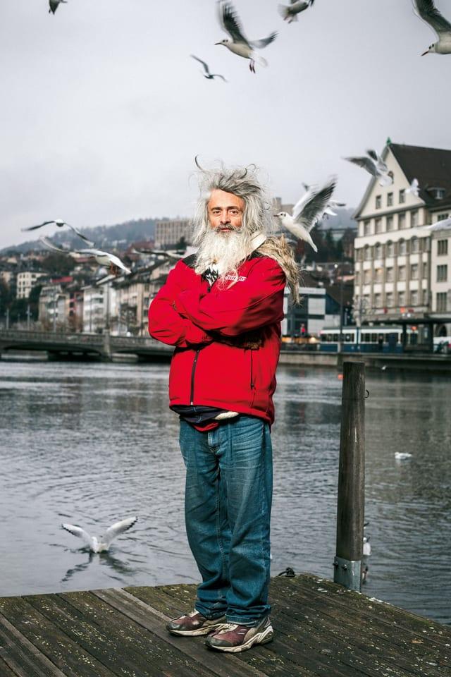 Ein Matt mit langem, zotteligen, weissen Haar, einer roten Windjacke, blauen Jeans und Turnschuhen. Er steht auf einem Steg in Zürich.