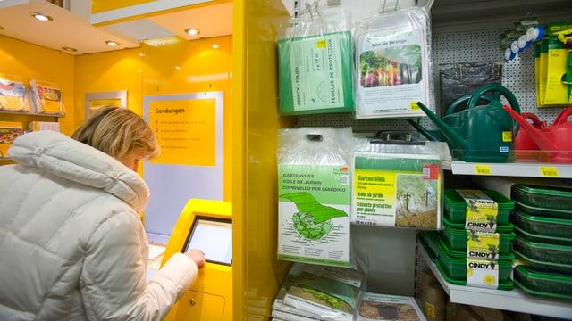 Frau erledigt Postgeschäft in einer Landi-Filiale.