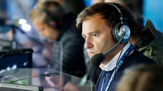 Sascha Ruefer mit ausgesetzten Kopfhörern und Mikrofon.