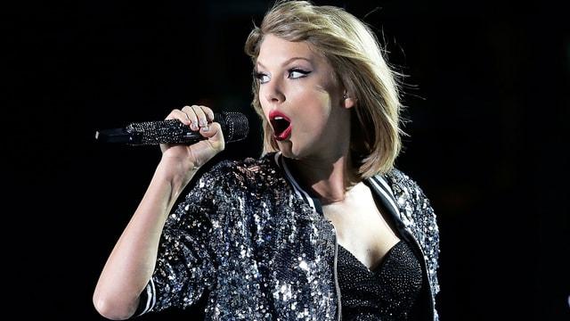 Taylor Swift singt ins Mikrofon.