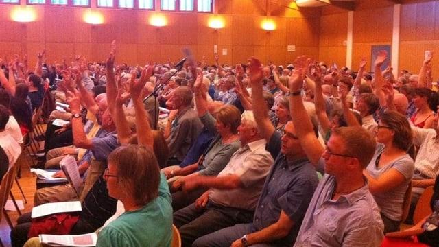 Gemeindeversammlung mit vielen Menschen, die abstimmen.