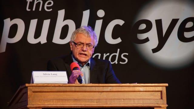 Um discurra sin il podi, davos l'inscripziun The Public Eye Awards.