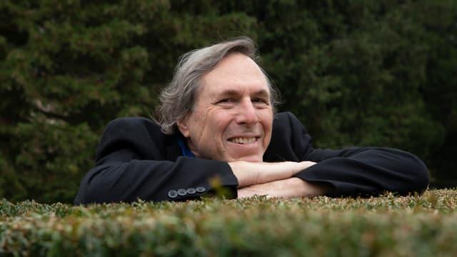 ein Mann stützt sich auf eine Gartenhecke auf