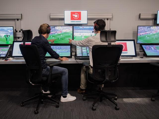 Zwei Personen vor Bildschirmen.