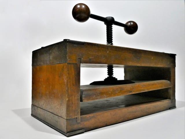 Eine Handpresse aus Holz und Metall.