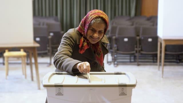 Eine ältere Frau legt ihren Abstimmungszettel in die Urne, aufgenommen im slowenischen Sora.