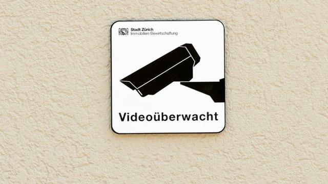 Ein Schild «videoüberwacht» an einer Hausmauer.